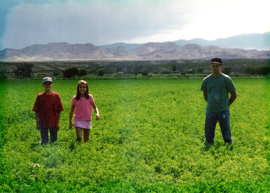 Chris, Steven, and Erica standing on the farm